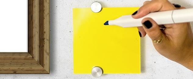 Eine Hand hält einen schwarzen Stift in der Hand und richtet diesen auf einen gelben Notizzettel.