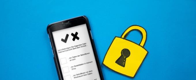 Auf dem Bildschrim eines Smartphones ist ein Formular zu sehen, während daneben ein gelbes Sicherheitsschloss aus Papier liegt.