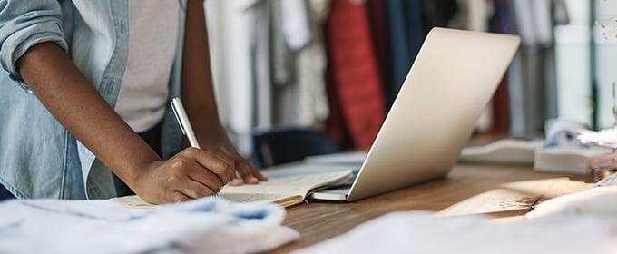 Eine Person steht auf einem aufgeklappten Laptop und macht sich Notizen.