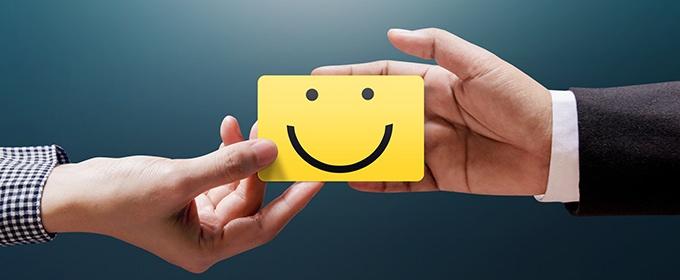 Eine Hand übergibt einer anderen einen gelben Zettel, auf dem ein lächelnder Smiley aufgemalt wurde.