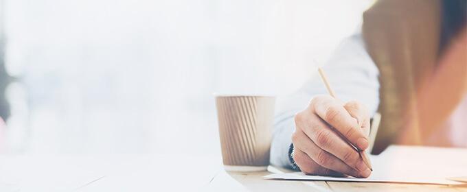 Jemand hält einen Bleistift in der Hand und schreibt auf einem Blatt Papier, während daneben ein Kaffeebecher steht.