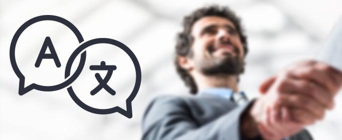 Menschen geben sich die Hand, während zwei Sprechblasen mit Buchstaben aus verschiedenen Sprachen zu sehen sind.