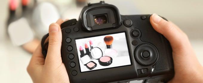 Jemand hält eine Kamera in den Händen, auf deren Display Kosmetikartikel zu sehen sind.