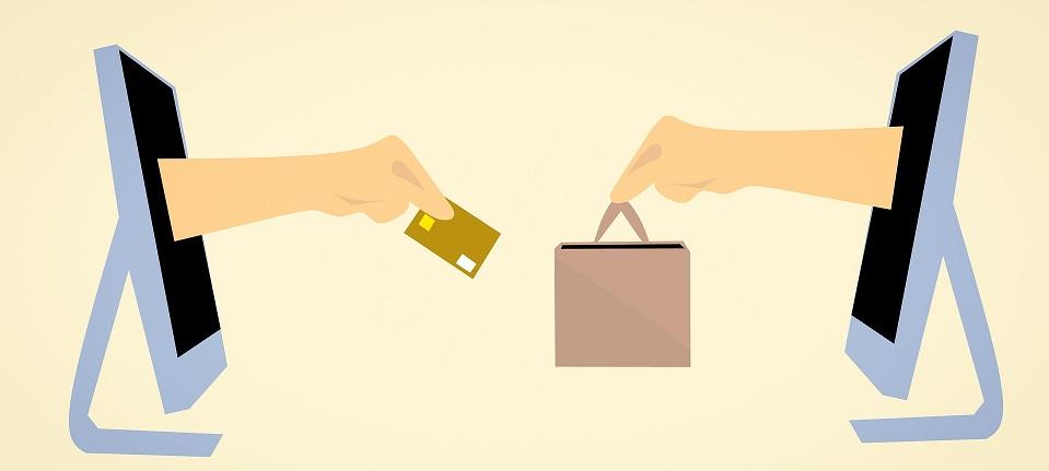 Aus zwei Computer-Bildschirmen kommen jeweils ein Arm: Der eine hält eine Kreditkarte in der Hand und der andere Arm eine Tasche.