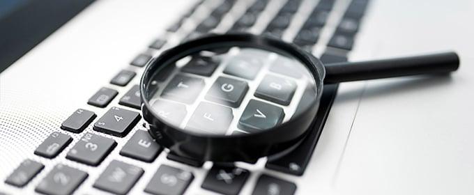 Eine schwarze Lupe liegt auf einer Computer-Tastatur.