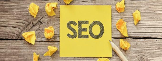 Auf einem gelben Notiznettel ist das Wort SEO mit einem Bleistift aufgemalt worden; neben dem Zettel liegen zerknüllte ebenfalls gelbe Zettel.
