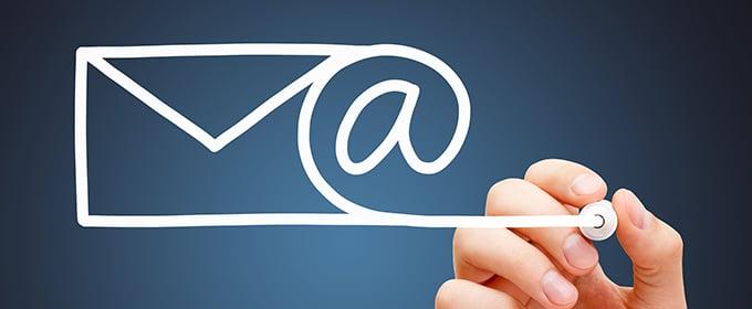 Jemand malt mit weißem Stift ein E-Mail-Symbol, welches in ein @-Zeichen übergeht.
