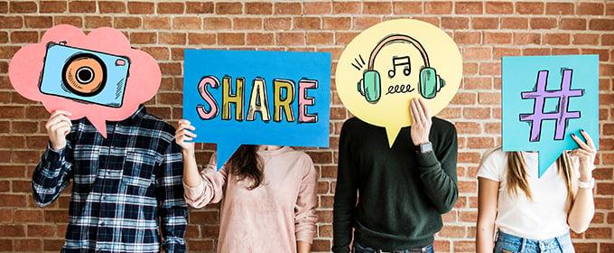 Vier Personen stehen nebeneinander und halten über ihren Köpfen Gesänge mit unterschiedlichen Symbolen in Bezug auf soziale Medien.