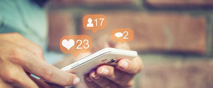 Jemand hält ein Smartphone in der Hand, während um das Telefon herum die Anzahl der Follower, Likes und Kommentare von etwas angezeigt werden.