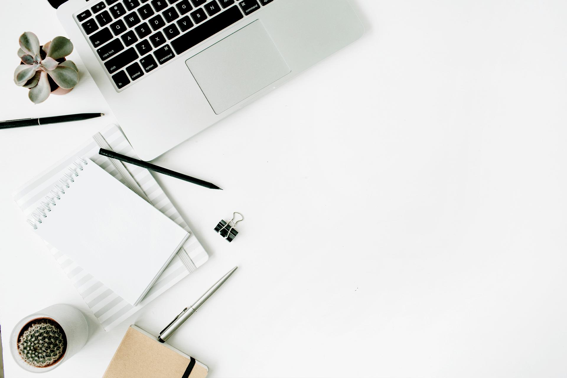 Ein geöffneter Laptop und mehrere Notizbücher mit Stiften liegen ordentlich auf einem weißen Untergrund.