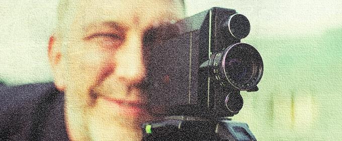 Ein Mann guckt durch die Linse einer Videokamera.