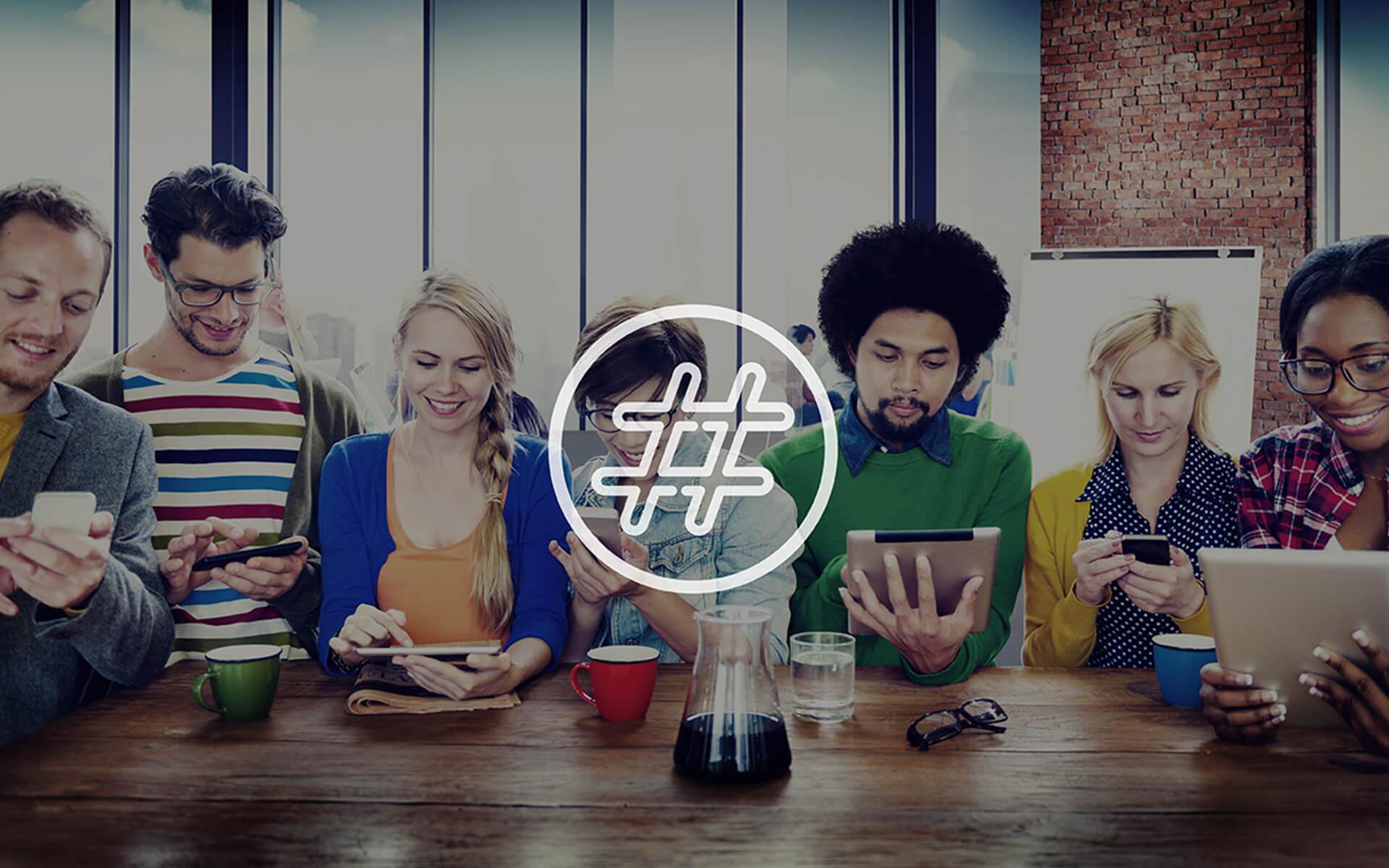 Fünf Personen sitzen zusammen und schauen auf ihre mobilen Geräte, während vorne das Symbol einer Raute zu sehen ist.