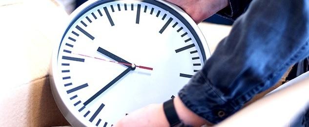 Jemand hält eine große Uhr in den Händen.