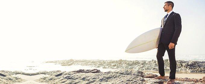 Mann im Business-Outfit mit Surfbrett am Strand im Sommer